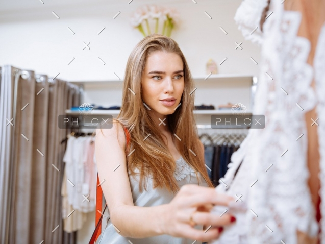 woman-doing-shopping-and-choosing-clothes-in-PDEP6XU